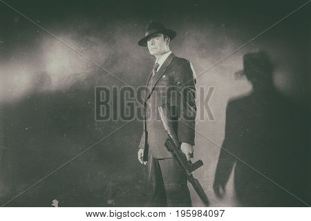 Antique Black And White Photo Of 1940S Film Noir Gangster Standing With Gun.