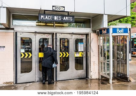 Montreal Canada - May 26 2017: People walking into Place des Arts metro station in city in Quebec region during wet rain on cloudy day