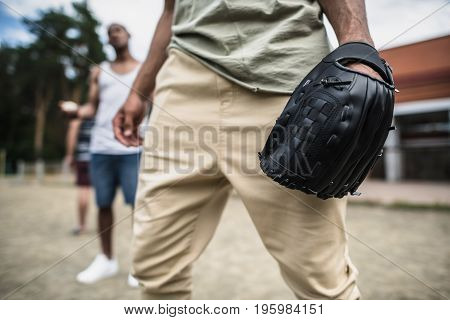 Cropped image of young man with baseball glove on hand