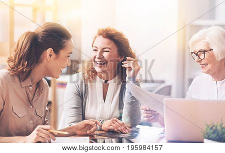 Enjoying the company. Excited humorous charming ladies spending their work time with pleasure and talking to each other while developing a new project