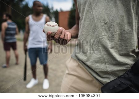 young handsome man with baseball ball in hand on court