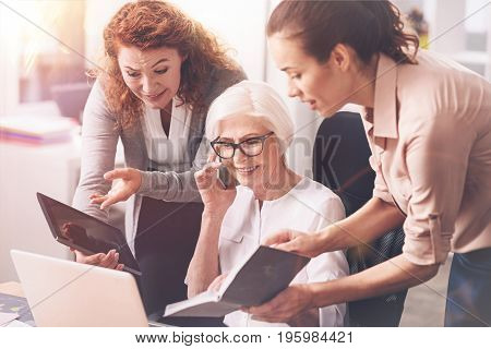 Can you find a minute. Busy charismatic elderly woman having a lot of work while her younger colleagues seeking her advice and asking for it insistently