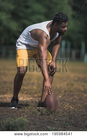 Young Handsome Male Football Player With Ball On Court