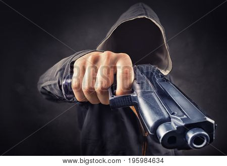 faceless man with a pistol in his hand