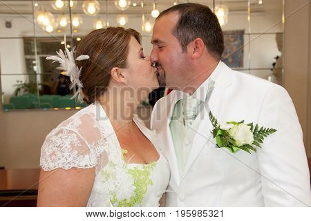 Two Young People In Love Standing In Town Council Registry Office On Their Wedding Ceremony, Kissing