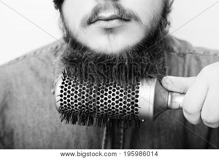 Portrait Of A Stylish Young Man Brushing His Beard