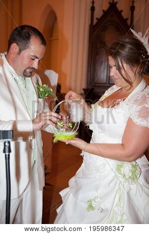 Groom Putting A Ring On Bride Finger During Wedding Ceremony