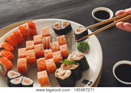 Eating roll sushi in japanese restaurant, hand with chopsticks closeup. Female has dinner