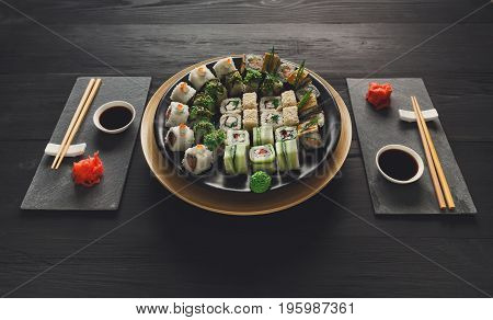 Japanese restaurant, eating sushi roll platter at rustic wood background. Set for two with chopsticks, ginger, soy, wasabi.