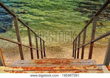 Rusty iron stairs descending into sea. Horizontal orientation