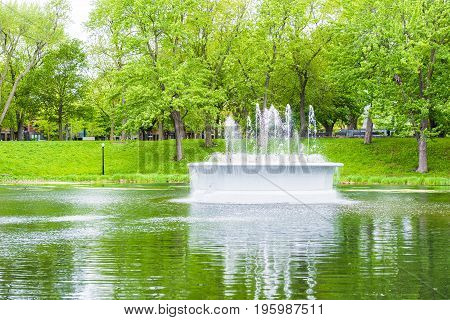 Montreal Canada - May 26 2017: Green fountain and lake in La Fontaine Park in Quebec region city during summer