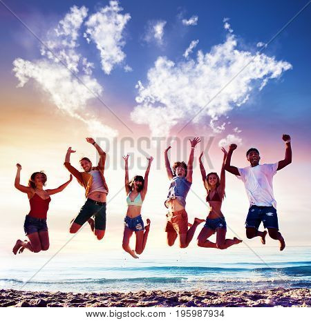 Happy smiling friends jumping over the sea of the beach over a blue sky with a world map made of clouds