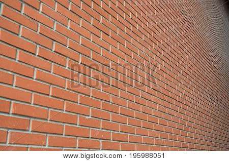 The Texture Of A High Brick Wall From A Many Rows Of Red Bricks Stretching Into Perspective