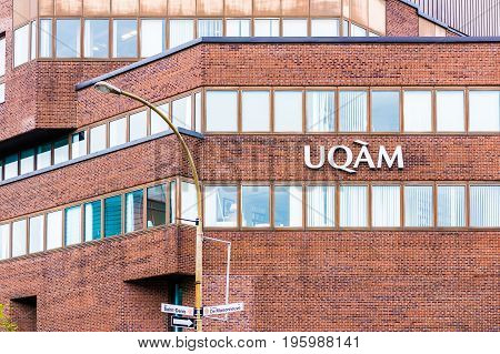 Montreal Canada - May 26 2017: UQAM University sign closeup brick building with rue Saint Denis and Boulevard de Maisonneuve