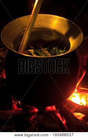 Big Pot on the camp fire in the evening. Spring mountains. Laos