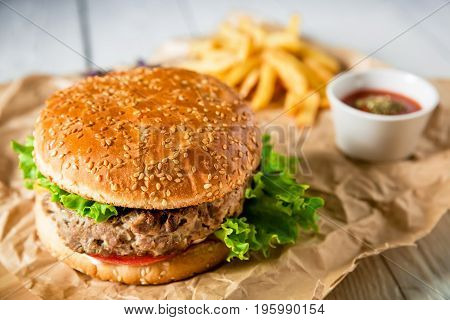 Tasty american hamburger with beef, sauce and french fries on wood background. Flat lay. Top view. American tasty food
