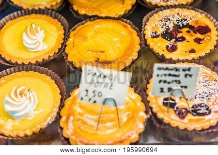 Small Lemon Meringue Tarts With Whipped Egg Whites On Display In Bakery With Signs In French