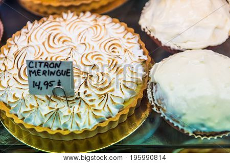 Lemon Meringue Tart With Whipped Egg Whites On Display In Bakery With Signs In French