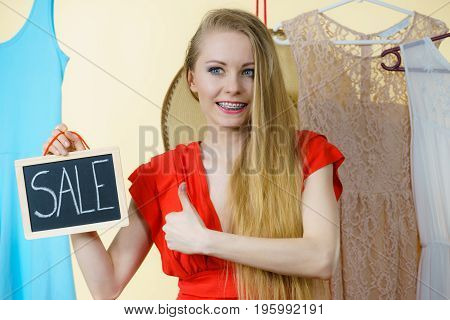 Woman In Shop With Sale Sign