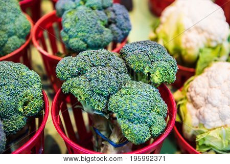 Closeup Of Broccoli And Cauliflower Bunches In Baskets On Display In Farmers Market