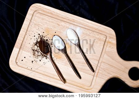 Coffee powder, Sugar, Creamer with wooden spoon on wooden plate - selective focus