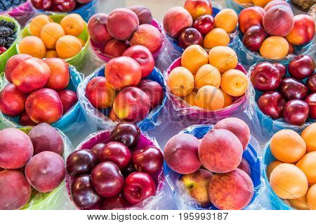 Closeup Of Many Summer Fruit In Baskets In Farmers Market On Display, Including Peaches, Plums, Nect
