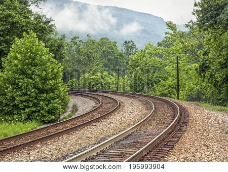 Double railroad tracks curve around a bend and into a misty mountain landscape in the Laurel Highlands of Pennsylvania.