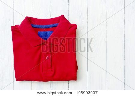 Top view close up of red polo shirt put on white wooden background tabletop