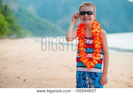 Boy In Flower Lei And Sunglasses On The Beach