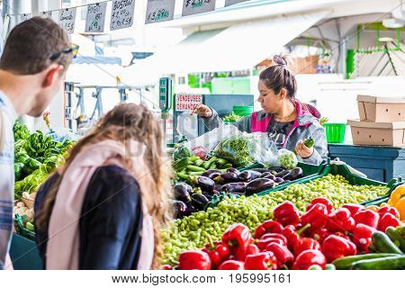 Montreal Canada - May 27 2017: Woman selling produce by vegetable stand with people buying at Jean-Talon farmers market with displays