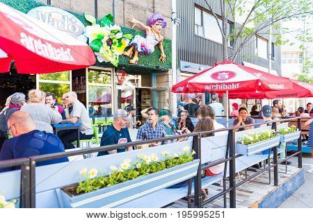 Montreal Canada - May 27 2017: People sitting in restaurant at table in outside seating area in Gay Village neighborhood in city in Quebec region