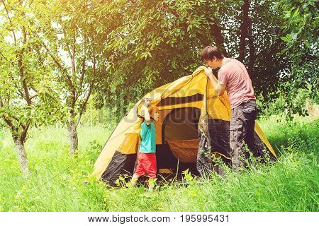 Happy father with son putting up tent together in woods.