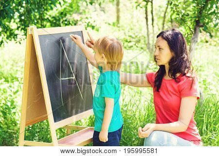 Mother and son are learning alphabet outdoor. Happy family.