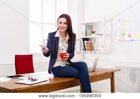 Coffee break. Cheerful businesswoman relaxing, sitting at workplace on office desk with cup of drink, smiling at camera