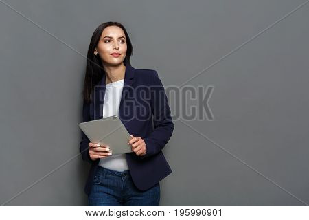 Elegant business woman in formal suit standing with tablet on gray studio background, looking away, copy space