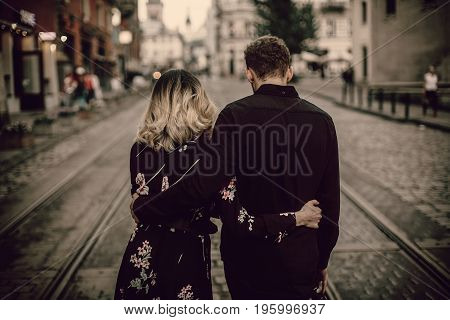 Stylish Gypsy Couple In Love Walking And Hugging In Evening City Street. Woman And Man Gently Embrac