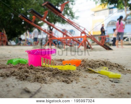 Toys for sand digging it have a beautiful color Lay on the sand. the background is a playground. have a children and adults.