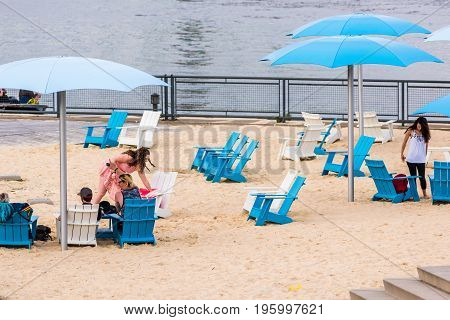 Montreal, Canada - May 27, 2017: Old Port Area Closeup Of People On Sandy Beach, Umbrellas In City I