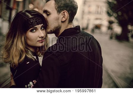 Stylish Gypsy Couple In Love Kissing Hugging In Evening City Street. Woman And Man Gently Embracing,
