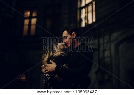 Stylish Gypsy Couple In Love Embracing In Evening City Street At Old Building. Woman And Man Gently