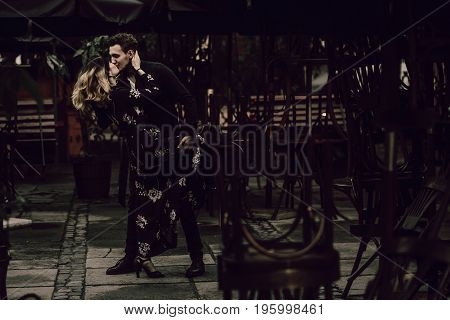 Stylish Gypsy Couple In Love Passionately Dancing In Evening City Street At Cafe Terrace. Woman And