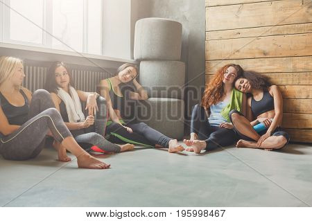 Girls in sportswear having rest after fitness training. Group of young fit women in sport club interior, pov. Sporty and healthy lifestyle concept