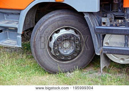 Front wheel of truck and part of car in green grass
