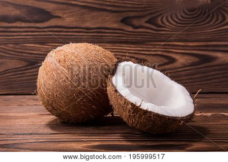 Two fresh brown hawaiian coconuts on a dark wooden background. Delicious white coconut cut in half and a whole brown coco. Healthy summer ingredients.