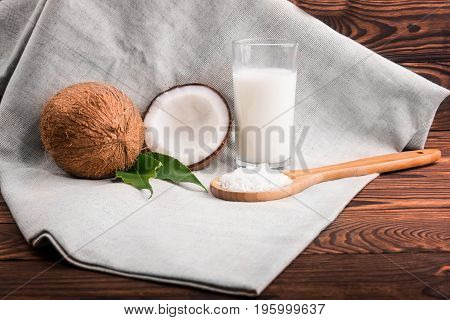 A transparent glass of coconuts, delicious coco milk, wooden spoon with coco chips on a gray bag on a wooden table. Whole and half fresh tropical coconuts with green leaves on the desk.