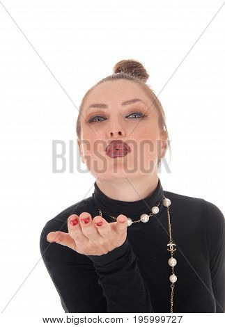 A gorgeous young woman in a black dress and a long necklace standing with one hand up and blowing a kiss isolated for white background.