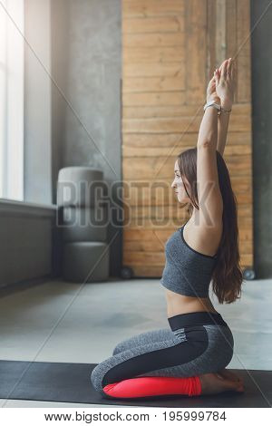 Attractive girl practicing yoga. Young woman in vajrasana with hands up doing breathing exercise on mat at sport club interior, copy space