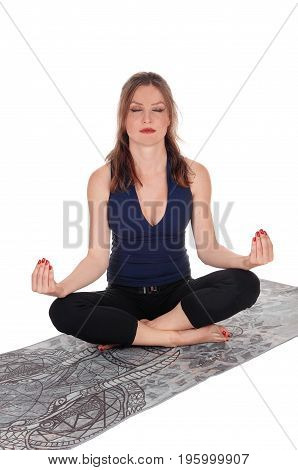 A brunette young woman sitting on a towel in a yoga pose with her eyes closed isolated over white background.