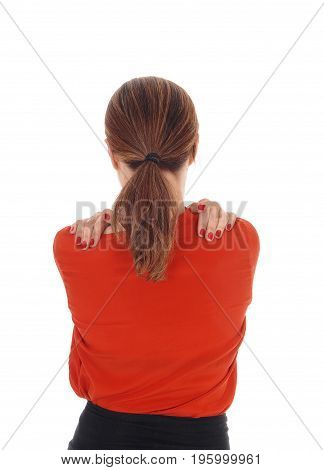 A young woman standing from the back in a closeup and hugging herself with her hands on her shoulder isolated for white background.