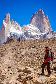 Male trekker standing on the rock in front of the stunning and impressive Mount Fitz Roy near El Chalten in Patagonia, Argentina poster